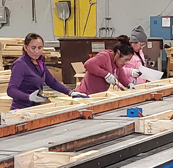 Three women working on a truss table