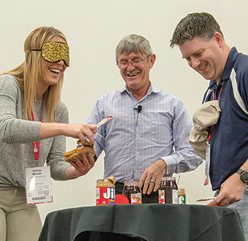 Two attendees at the safety summit participate in a funny safety lesson and make sandwiches blindfolded