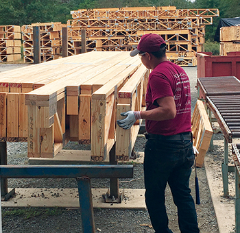 A man handles trusses wearing eye protection and gloves