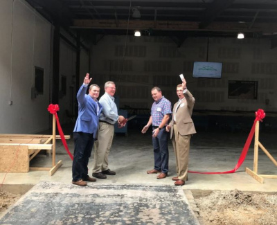 Four men cutting the ribbon to celebrate the company's expansion