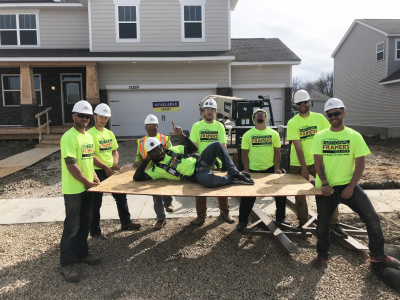 Group of construction guys in Stand-Down shirts holding a plyboard with a worker laying across it