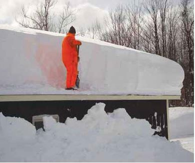 Man shoveling snow off a roof