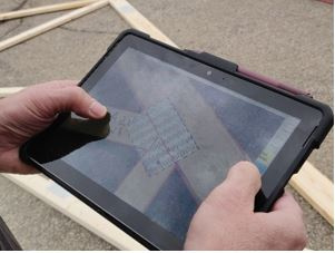 Hands holding an ipad with the digital qc software