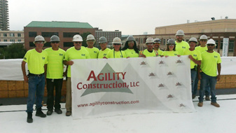 Group of workers in hard hats and safety yellow shirts holding an Agility Construction banner