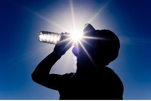 Person drinking from a bottled water in the sun