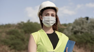 A women in construction wearing a face mask