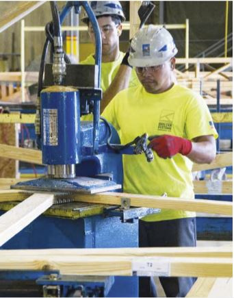 Worker at Shelter Systems pressing a connection plate to a truss